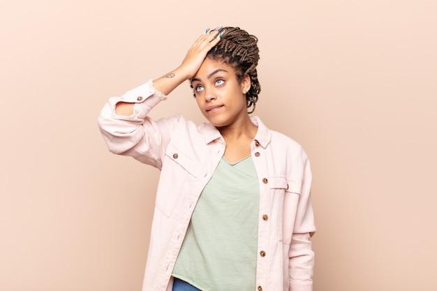 Giovane donna afro che alza il palmo alla fronte pensando oops