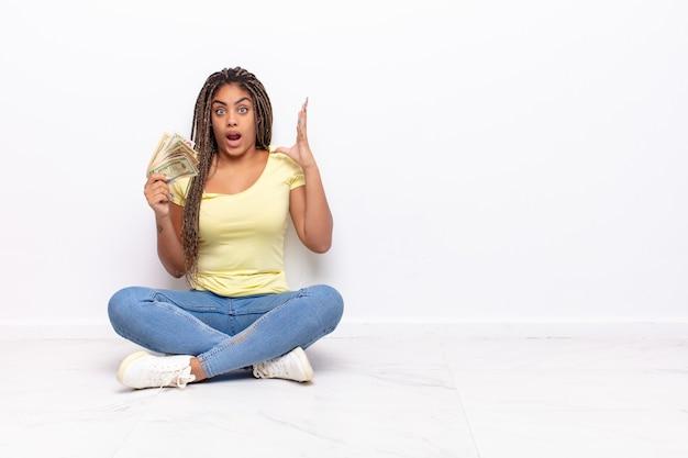 Giovane donna afro che grida con le mani in aria, sentendosi furiosa, frustrata, stressata e sconvolta. concetto di denaro