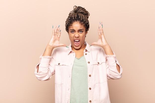 Giovane donna afro che grida con le mani in alto, sentendosi furiosa, frustrata, stressata e sconvolta