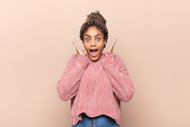 Giovane donna afro che grida con le mani in alto nell'aria isolata