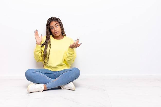 Giovane donna afro che scrolla le spalle con un'espressione stupida, pazza, confusa, perplessa isolata