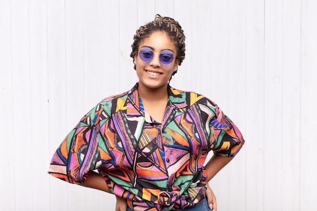 Giovane donna afro che sorride allegramente e casualmente con un'espressione positiva, felice, sicura e rilassata