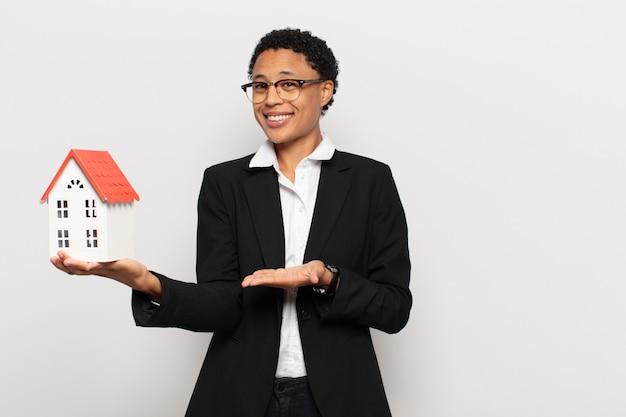Giovane donna afro che sorride allegramente, sentendosi felice e mostrando un concetto nello spazio della copia con il palmo della mano