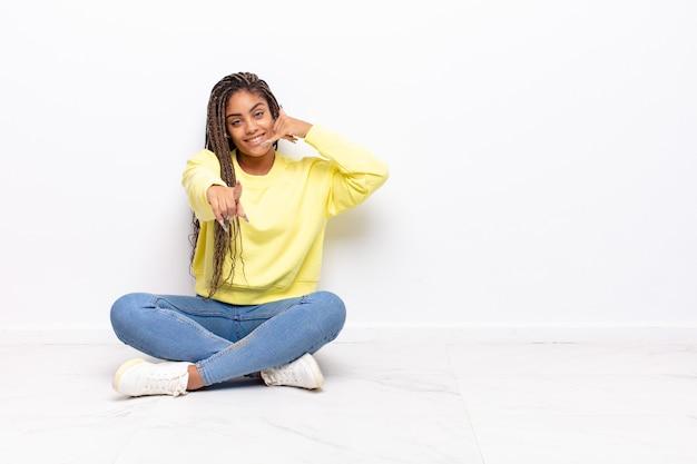 Giovane donna afro che sorride allegramente e punta davanti mentre effettua una chiamata in seguito gesto, parlando al telefono