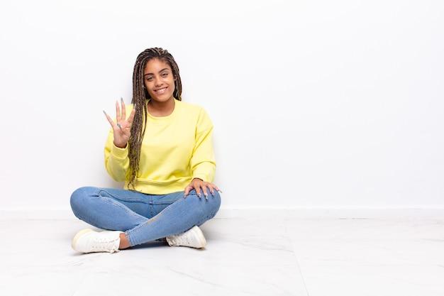 Giovane donna afro sorridente e dall'aspetto amichevole, mostrando il numero quattro o il quarto con la mano in avanti, conto alla rovescia