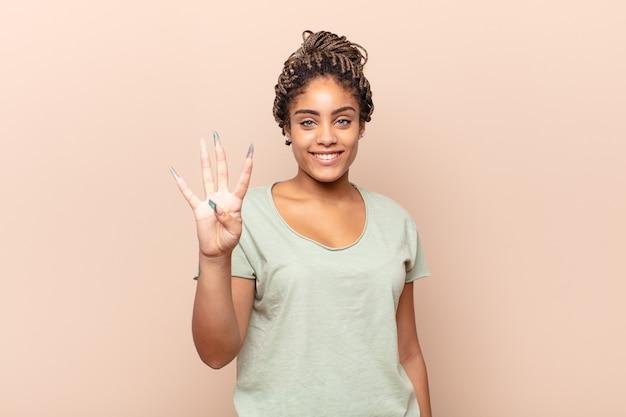 Giovane donna afro sorridente e guardando amichevole, mostrando il numero quattro o quarto con la mano in avanti