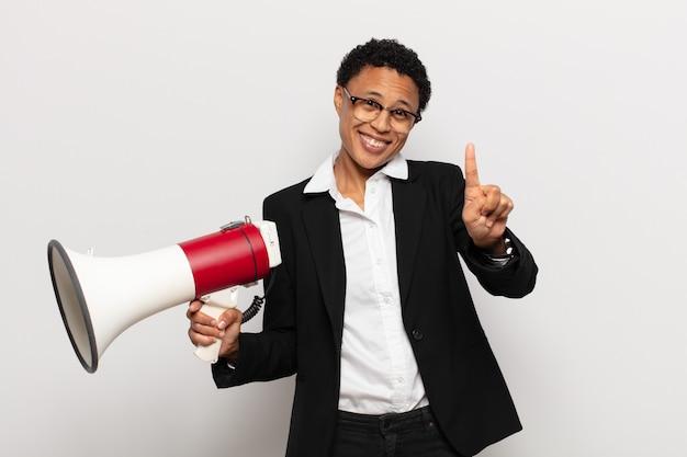 Giovane donna afro sorridente e guardando amichevole, mostrando il numero uno o il primo con la mano in avanti, il conto alla rovescia