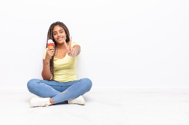 Giovane donna afro che sorride e che sembra felice, spensierata e positiva