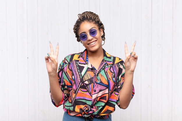 Giovane donna afro che sorride e che sembra felice, amichevole e soddisfatta, gesticolando vittoria o pace con entrambe le mani