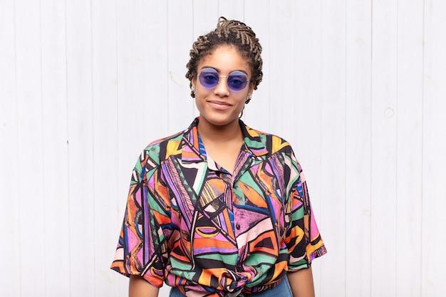 Giovane donna afro che sorride positivamente e con sicurezza isolata