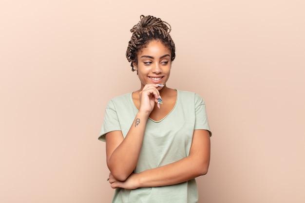 Giovane donna afro che sorride con un'espressione felice e sicura con la mano sul mento, chiedendosi e guardando di lato