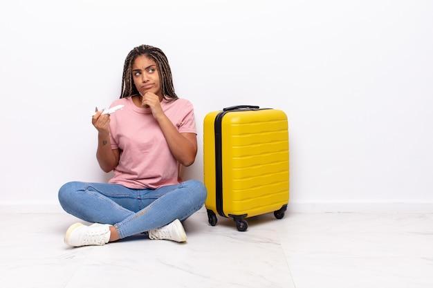 Giovane donna afro che pensa, si sente dubbiosa e confusa, con diverse opzioni, chiedendosi quale decisione prendere. concetto di vacanze