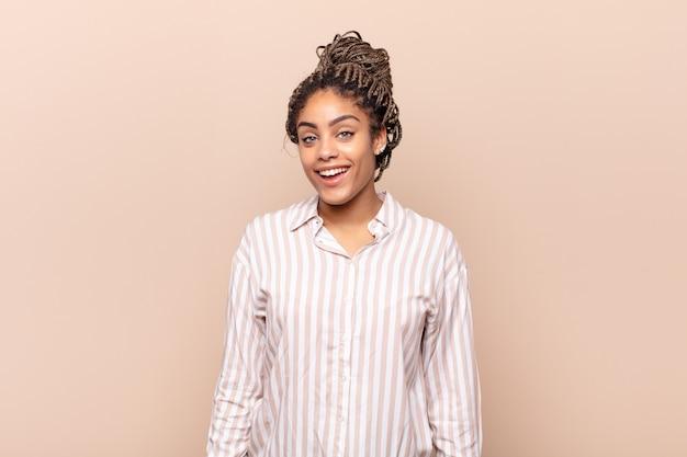 Giovane donna afro con un sorriso grande, amichevole e spensierato, dall'aspetto positivo, rilassato e felice, agghiacciante