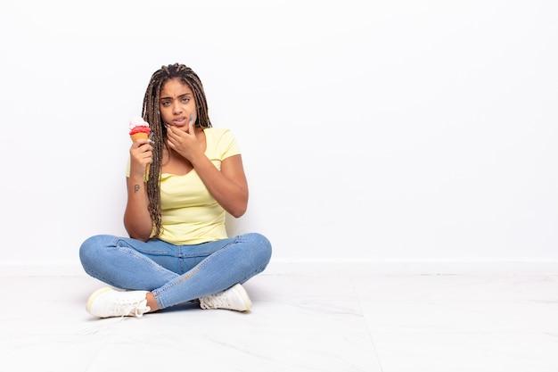 Giovane donna afro con la bocca e gli occhi spalancati e la mano sul mento