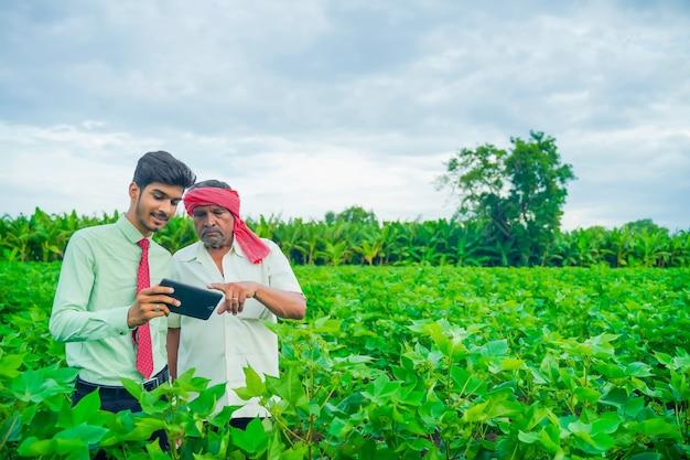 Giovane agronomo e agricoltore ispezionando il campo di cotone con tablet
