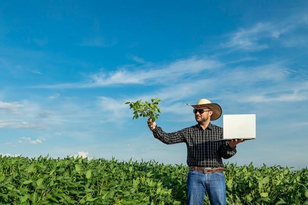 Giovane agronomo in cappello che tiene il taccuino nel campo di soia.