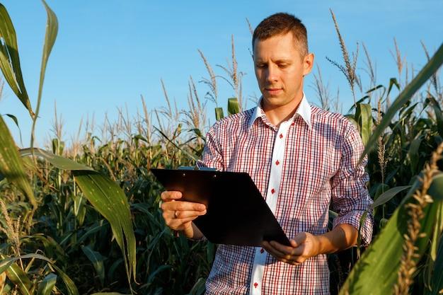 Il giovane agronomo tiene in mano un grafico cartaceo e analizza il raccolto di mais