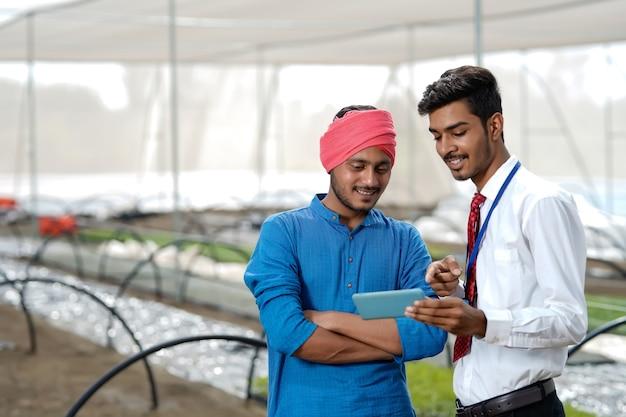 Giovane agronomo che mostra alcune informazioni all'agricoltore in smartphone in serra