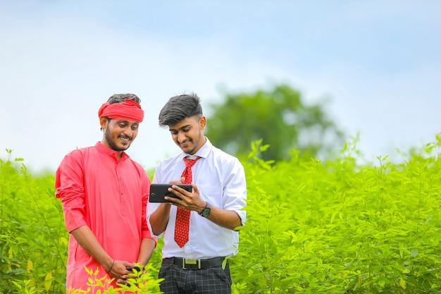 Giovane agronomo che mostra alcune informazioni in tablet all'agricoltore al campo verde
