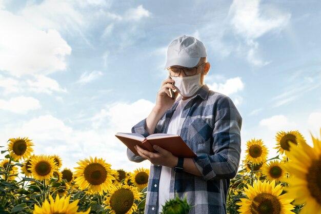 Giovane agronomo con maschera facciale che lavora nel campo di girasole