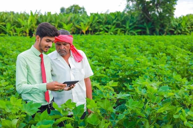 Giovane agronomo con agricoltore ispezionando nel campo di cotone con tablet