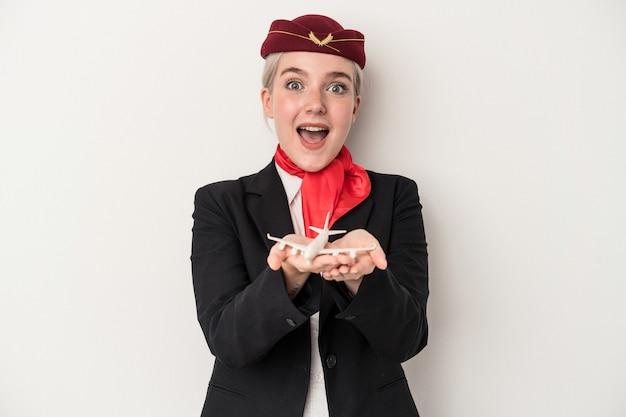 Giovane hostess donna caucasica che tiene aereo isolato su sfondo bianco