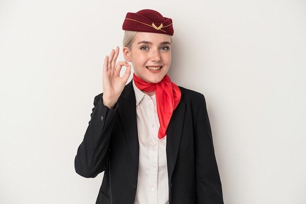 Giovane donna caucasica dell'assistente di volo isolata su fondo bianco allegro e sicuro che mostra gesto giusto.