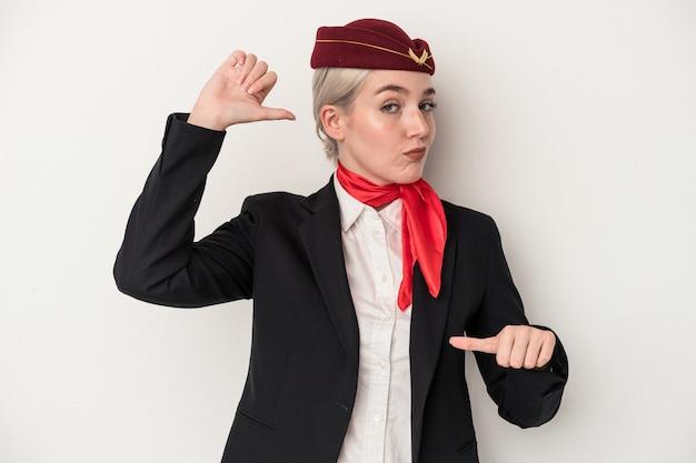 La giovane donna caucasica hostess isolata su sfondo bianco si sente orgogliosa e sicura di sé, esempio da seguire.