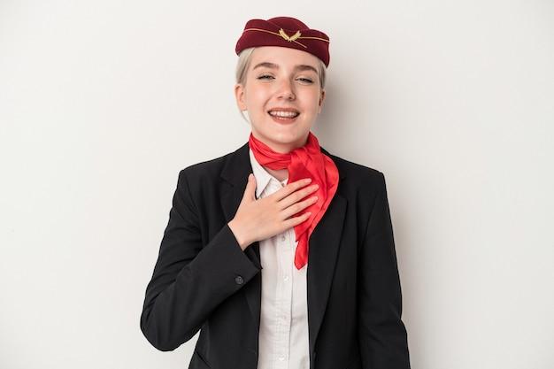 La giovane donna caucasica dell'assistente di volo isolata su fondo bianco ride ad alta voce tenendo la mano sul petto.