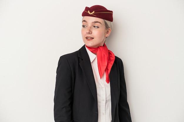 La giovane donna caucasica dell'assistente di volo isolata su fondo bianco guarda da parte sorridente, allegra e piacevole.