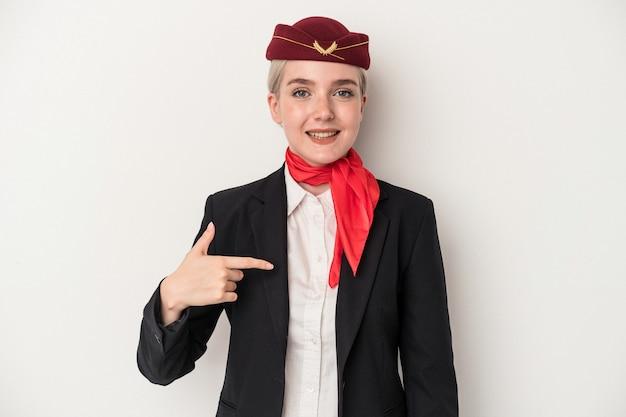 Giovane donna caucasica hostess isolata su sfondo bianco persona che indica a mano uno spazio copia camicia, orgogliosa e sicura di sé