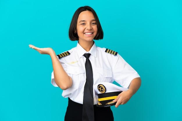 Giovane pilota di aeroplano su sfondo blu isolato che estende le mani di lato per invitare a venire