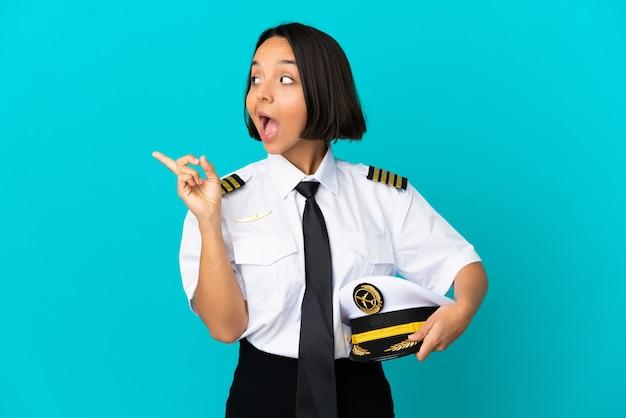 Giovane pilota di aeroplano su sfondo blu isolato con l'intenzione di realizzare la soluzione mentre si solleva un dito