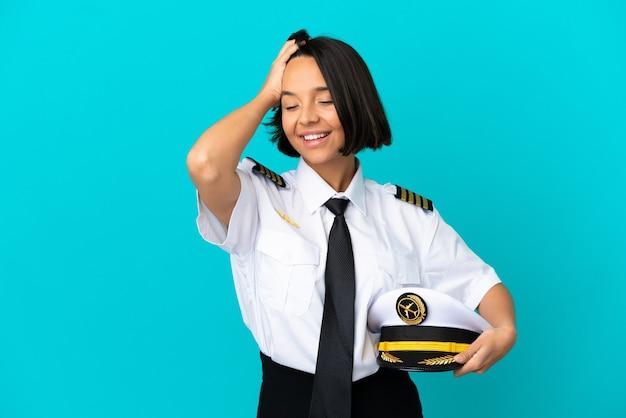Giovane pilota di aeroplano su sfondo blu isolato ridendo