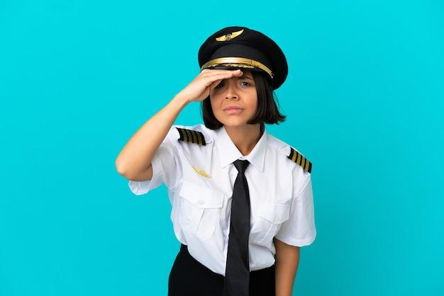 Giovane pilota di aeroplano su sfondo blu isolato guardando lontano con la mano per guardare qualcosa