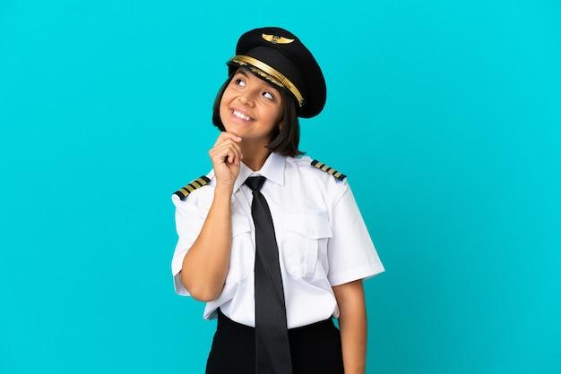 Giovane pilota di aeroplano su sfondo blu isolato guardando in alto sorridendo