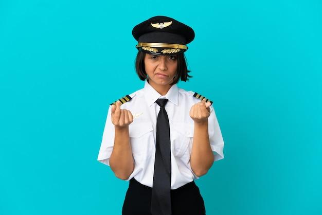 Giovane pilota di aeroplano su sfondo blu isolato che fa un gesto di denaro ma è rovinato