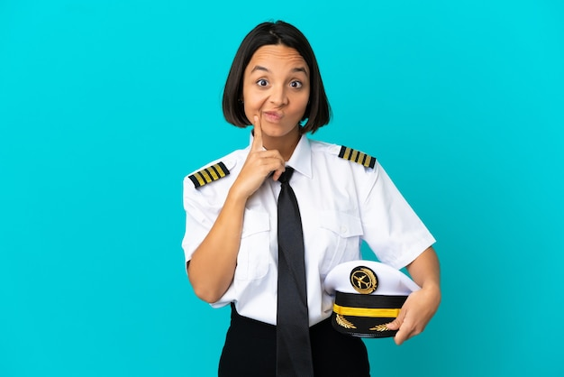 Giovane pilota di aeroplano su sfondo blu isolato e pensiero