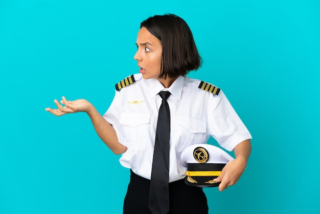 Giovane pilota di aeroplano su sfondo blu isolato con espressione di sorpresa mentre guarda di lato