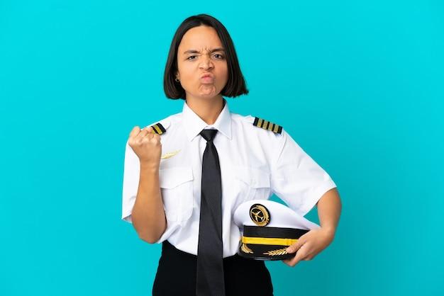 Giovane pilota di aeroplano su sfondo blu isolato con espressione infelice