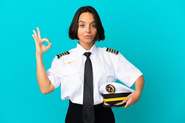 Giovane pilota di aeroplano su sfondo blu isolato in posa zen
