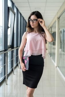 Giovane imprenditrice sola con blocco note in piedi nel centro business. pausa caffè