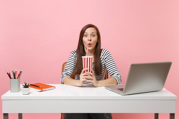 Giovane donna stupita e divertente che tiene in mano una tazza plactic con cola o soda, si siede alla scrivania bianca con un computer portatile contemporaneo