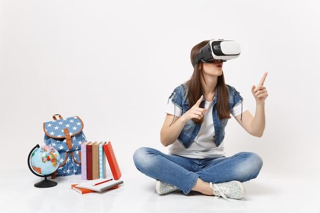 Giovane studentessa stupita in occhiali per realtà virtuale che punta il dito indice in alto seduto vicino a globo, zaino, libri di scuola isolati su muro bianco