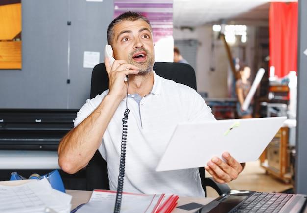 Giovane e ambizioso commerciante di borsa sta facendo un affare al telefono in un ufficio pieno di computer.