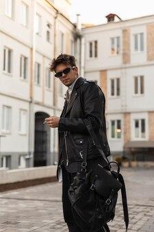 Hipster di giovane uomo americano in occhiali da sole alla moda in giacca di pelle nera alla moda in jeans vintage con zaino fuma nel cortile vicino agli edifici. il ragazzo figo sta con la sigaretta in città.