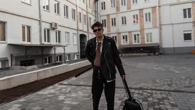 Il giovane hipster americano in occhiali da sole alla moda in una giacca di pelle alla moda in jeans neri con zaino cammina nel cortile vicino agli edifici. il modello di ragazzo cool si trova in città. abbigliamento maschile giovanile.