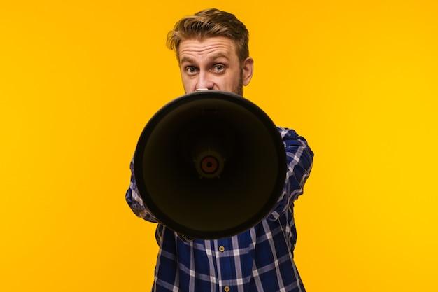 Giovane uomo americano sul giallo vibrante che grida tramite un megafono per annunciare qualcosa