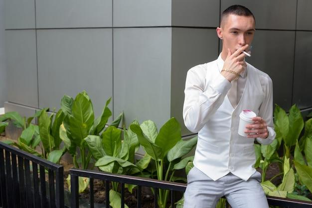 Giovane imprenditore androgino bere caffè e fumare sigarette