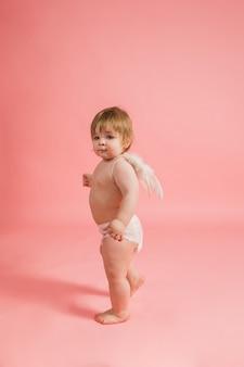 Giovane angelo in un pannolino e con le ali su una parete rosa